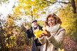 canvas print picture - Senior couple on a walk in a forest in an autumn nature, holding leaves.