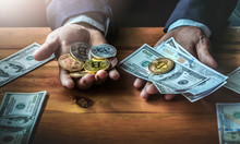 Close Up Businessman Holding Money And Bitcoin On Wooden Desk