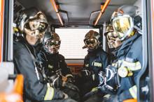 Unrecognizable Firemen With Helmet In An Emergency Vehicle