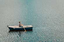 Man With Hat In Rowing Boat On Lake In The Black Forest - Schluchsee, Germany