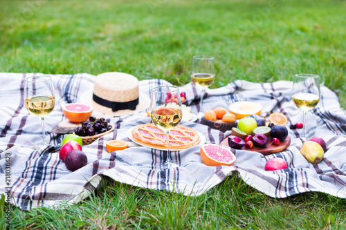 Keuken foto achterwand Picknick Picnic background with white wine and summer fruits on green grass, summertime party