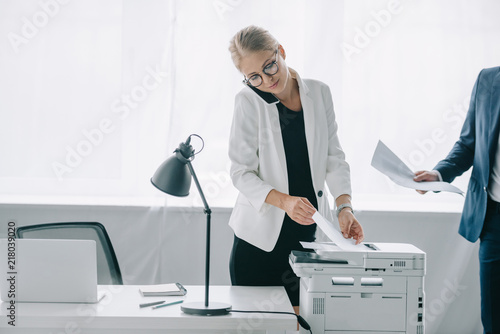 Fotografía  businesswoman talking on smartphone while using printer in office with colleague
