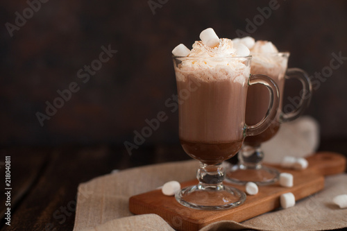 Foto op Plexiglas Chocolade Two glasses with Hot chocolate garnished with whipped cream, marsmallow and cocoa powder.