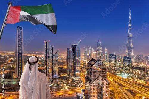Fototapeta premium Arabski mężczyzna ogląda nocny panoramę Dubaju z nowoczesną futurystyczną architekturą w Zjednoczonych Emiratach Arabskich