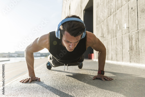Fit athlete doing push ups at the river