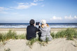 Couple sitting in dunes on the beach with tablet