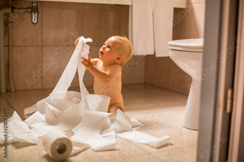 Fotografia Toddler baby boy, ripping up with toilet paper in bathroom.