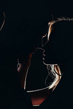 Silhouettes Of Young Tender Couple Going To Kiss In Dark