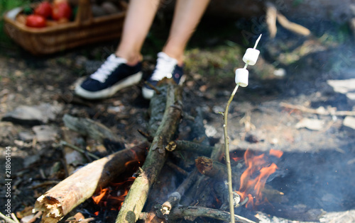 Keuken foto achterwand Picknick How to roast marshmallows. Marshmallows on stick with bonfire and smoke on background. Roasty, toasty marshmallows are such quintessential taste of picnic. Holding a marshmallow on stick