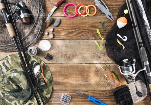 Foto op Aluminium fishing rods with lures and hooks on wooden table. fishing background
