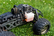 Radio-controlled Car With Internal Combustion Engine For Nitro Fuel, With One Cylinder, Standing On Green Grass.