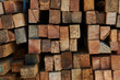Background of the square ends of the wooden bars. Wood timber construction material for background and texture. Close up. Stack of wooden bars. Small depth of field. Pile of old wooden boards.