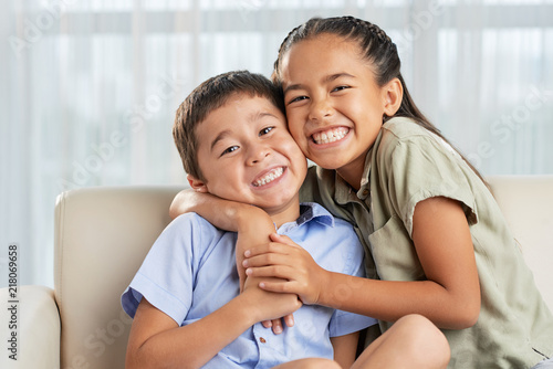 Fotografie, Obraz Cheerful Asian girl smiling and embracing cute boy while sitting on comfortable