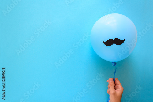 Hand holding blue balloon with a paper mustache on blue paper background Canvas Print