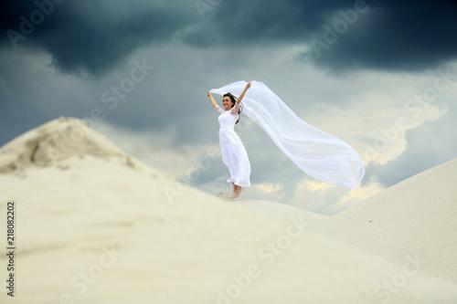 Piękna dziewczyna w białej sukni ślubnej z długim welonem na piaszczystej wydmie. - fototapety na wymiar