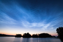 Night Shining Clouds Over Lake In Finland