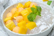 The thai dessert food modern style : The homemade sago in coconut milk with topping is mango cut into squares and cantaloupe ball in the white bowl and placed on tablecloth plaid on the marble table.