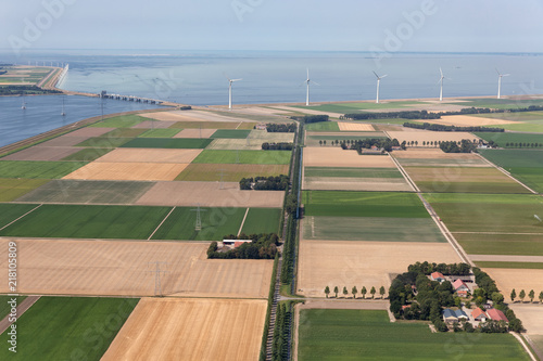 Fotografía Aerial view Dutch agricultural landscape with row offshore wind turbines along t