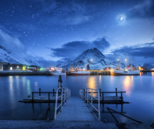 Fishing Boats Near Pier On The Sea Against Snowy Mountains And Starry Sky With Moon At Night In Lofoten Islands, Norway. Winter Landscape With Ship, Buildings, Illumination, High Rocks And Clouds