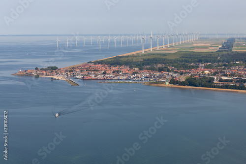 Foto op Aluminium Luchtfoto Aerial view Dutch fishing village with harbor and big offshore wind turbines along the coast