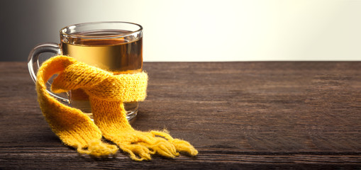 Healing glass of tea in a scarf on a wooden background