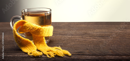 Staande foto Thee Healing glass of tea in a scarf on a wooden background