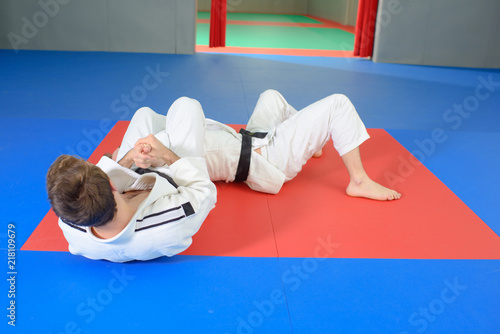 People in martial arts hold on floor