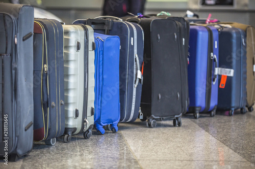 Wheeled suitcases on a floor near the luggage belt at the airport terminal.