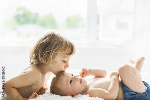 Carta da parati baby in bed with his brother son giving a kiss