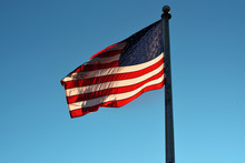 A US Flag Flying With The Sun Behind It Against A Beautiful Blue Sky.