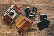 Vintage 35mm Film Camera In Worn Leather Case With Film Canisters And Prints On Weathered Wooden Background