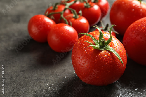 Tasty juicy tomatoes on grey background, closeup