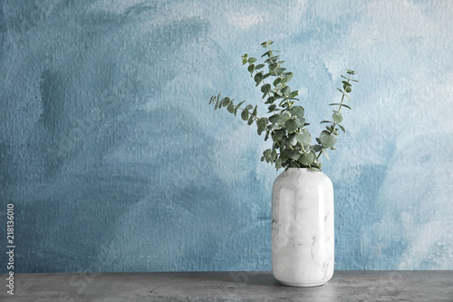 Fotografia  Bunch of eucalyptus branches with fresh leaves in vase on table