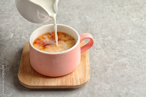 Pouring milk into cup of black tea on gray table