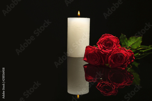 Fotomural Beautiful red roses and candle on black background