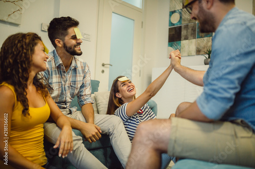 Fotografie, Obraz  Happy friends playing game guess who and having fun at home