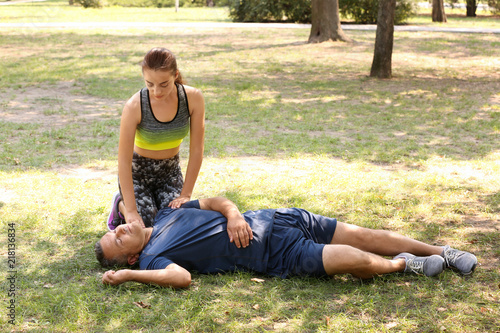Fotografie, Obraz  Woman checking pulse of unconscious man outdoors