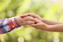 Young Woman Holding Elderly Man Hand On Blurred Background, Closeup. Help Service