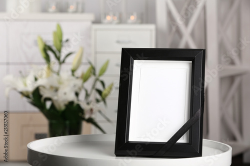 Funeral photo frame with black ribbon on table, indoors