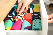 Woman Opening Drawer With Different Colorful Socks Indoors, Closeup