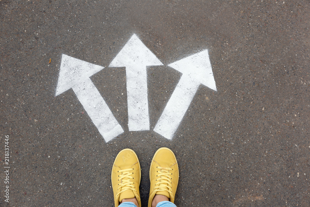 Fototapeta Woman standing near arrows on asphalt, top view. Choice concept