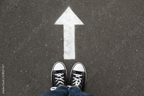 Photo  Woman standing near arrow on asphalt, top view. Choice concept