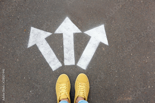 Photo Woman standing near arrows on asphalt, top view. Choice concept