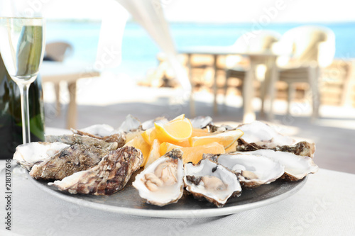 Fresh oysters with cut juicy lemon served on table