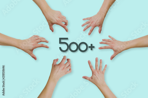 Foto  Top view of hands reaching for the social program in Poland 500+