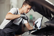 A young and attractive mechanic is checking an oil level of a car engine