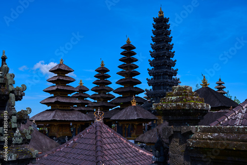 Roofs of Pura Besakih temple, Bali, Indonesia on the bright blue sky background. Traditional balinese architecture. Buddhist pagodas. Main Bali temple Pura Besakih at the foot of the volcano Agung.