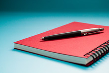 Red Notebook And Pen On Blue T...