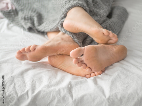Couple in bed playing footsie. Love and relationship concept. Canvas Print