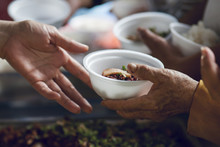 Hands Of The Poor Receive Food From The Donor's Share. Poverty Concept
